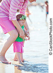 mom and baby on beach have fun - happy mom and baby on beach...