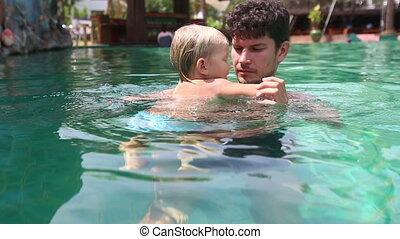 father swims with little daughter in pool