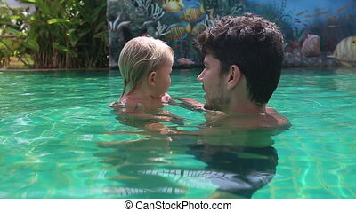 young father learns to dive blonde little daughter in swimming pool
