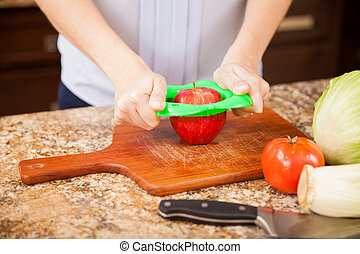 Slicing an apple in the kitchen - Closeup of a woman using...