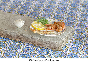 Plate of shrimp, lemon, bread and dill, side view