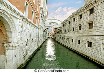 Gondola on small canal passing towards famous Bridge of...