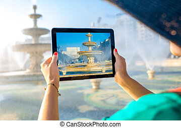 Photographing central fountain in Bucharest - Young female...