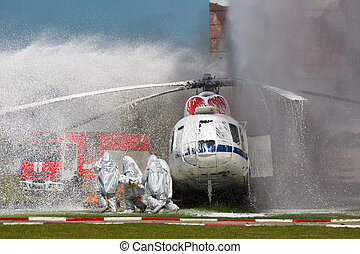 Firefighters in special suits extinguish the fire by...