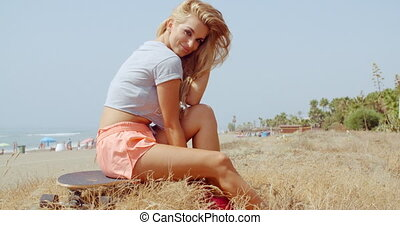 Girl Resting on her Skateboard on a Grassy Ground -...