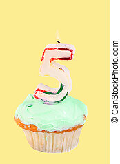 fifth birthday cupcake with green frosting on a yellow...