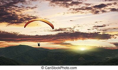 Paragliding at sunset with purple clouds