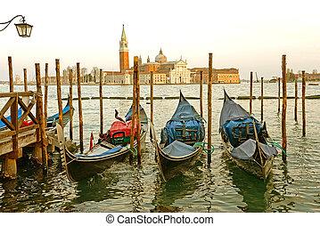 Gondolas moored by Saint Mark square with San Giorgio di Maggiore church in the background - Venice, Venezia, Italy, Europe