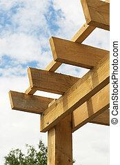 Closeup shot at the corner of a wooden pergola against blue...