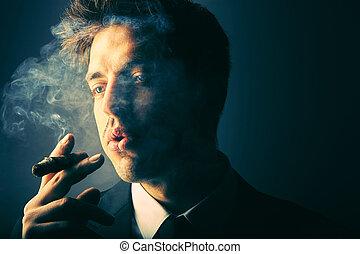 Handsome young man smoking cigar