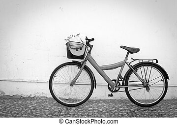 red bicycle - bicycle on black and white old house wall