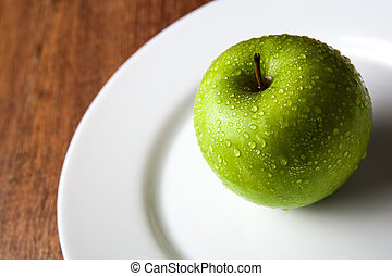 fresh green apple on a white plate close up