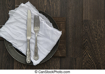 Vintage cutlery on muslin cloth on pewter plate with rustic...