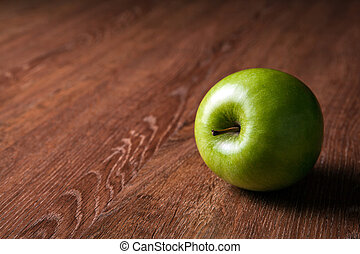 fresh green apple on a wooden table close up