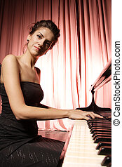woman playing piano - A beautiful young woman playing piano...