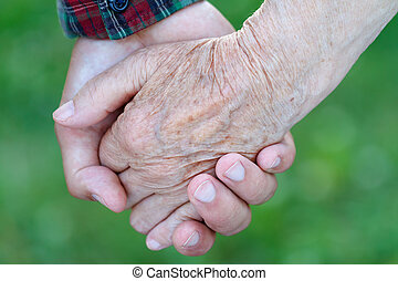 Helpful hands - Young male hand holding an elderly woman's...