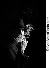 a man in a grey hat on black background smoking a cigarette...