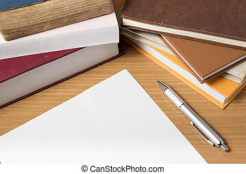 empty paper and pen with book on wood background