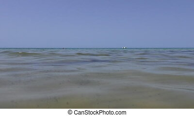 Sea ripples, swimmers boat horizon - Abstract footage...