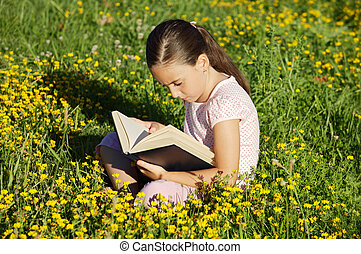 Reading a book - Girl reading a book on the grass
