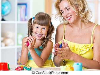 kid and mother play colorful clay toy at home - kid girl and...