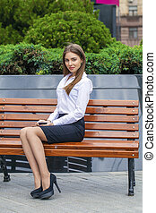 Beautiful business woman sitting on a bench - Young...