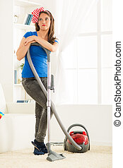 Housewife With Vacuum Cleaner - A young housewife standing...