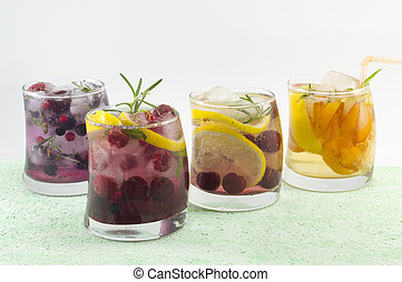 Four non alcoholic fruit cocktails arranged on the green table with white background. Summer drinks.