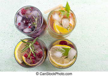 Four non alcoholic fruit cocktails arranged on the green...