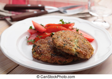Fish cakes with salad - Fish cakes with tomato salad on a...