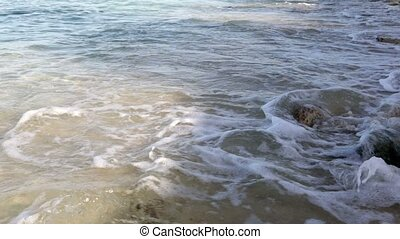 Sandy beach with rocks and waves