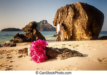 bride and groom barefoot stand and hug against cliff with...