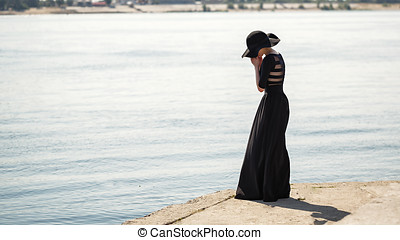 Ballerina in hat and long black dress sad.