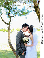 romantic newlywed couple touching forehead under the tree