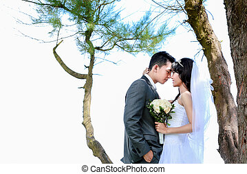 romantic newlywed couple touching forehead under the tree...