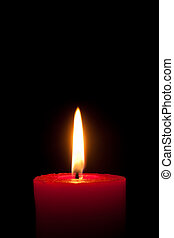 A red candle in front of black background, isolated - A...