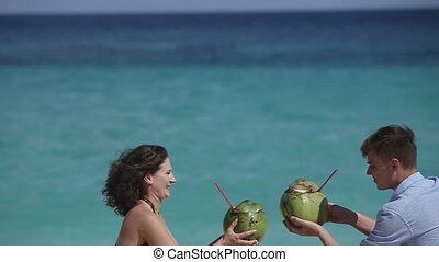 Happy couple on the beach with coconut - Young loving happy...
