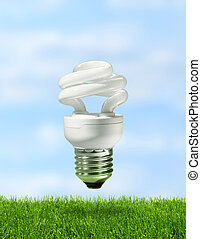 Energy saving compact fluorescent lamp over green grass with...