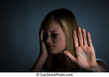 Girl in pain - Young blonde girl with bruised face holds...