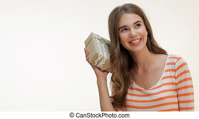 Beautiful woman shaking a gift present - Brown-haired...