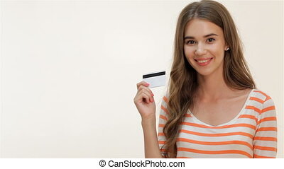 Attractive girl showing thumbs-up with credit card -...