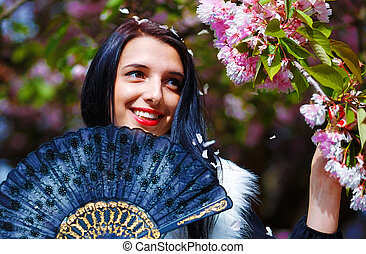 woman with flowers, glamour white fur and black fan in hand,...