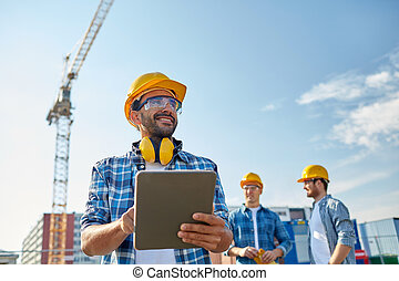 builder in hardhat with tablet pc at construction -...