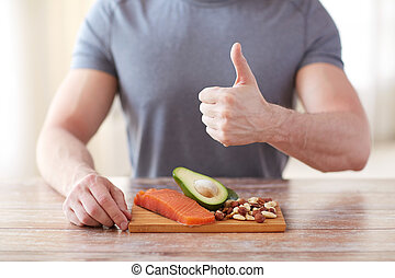 close up of male hands with food rich in protein - healthy...