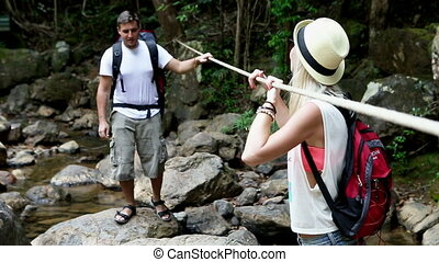 Jungle Adventure - Tourist couple crossing mountain river...