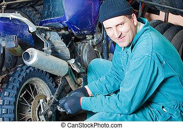 mechanic in garage - mechanic changing car tire in garage