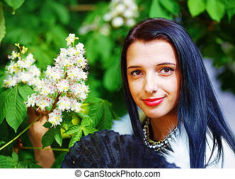 Beautiful Girl with flowers, glamour white fur, posing next...