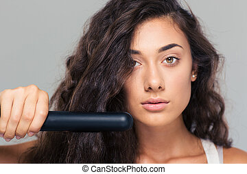 Woman doing hairstyle with hair straightener - Closeup...