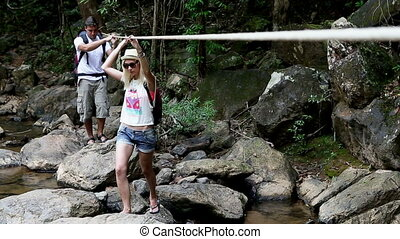 Crossing Mountain River - Couple of backpackers walking on...