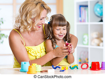 child with mom making by hands - kid girl and mom play with...
